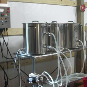 Three 20 gallon pots on a stainless table, with valves, fittings, tubing, 2 pumps, an electric control panel and a stainless conical fermenter.